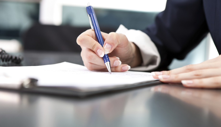 Mann unterschreibt Formular mit Kugelschreiber
